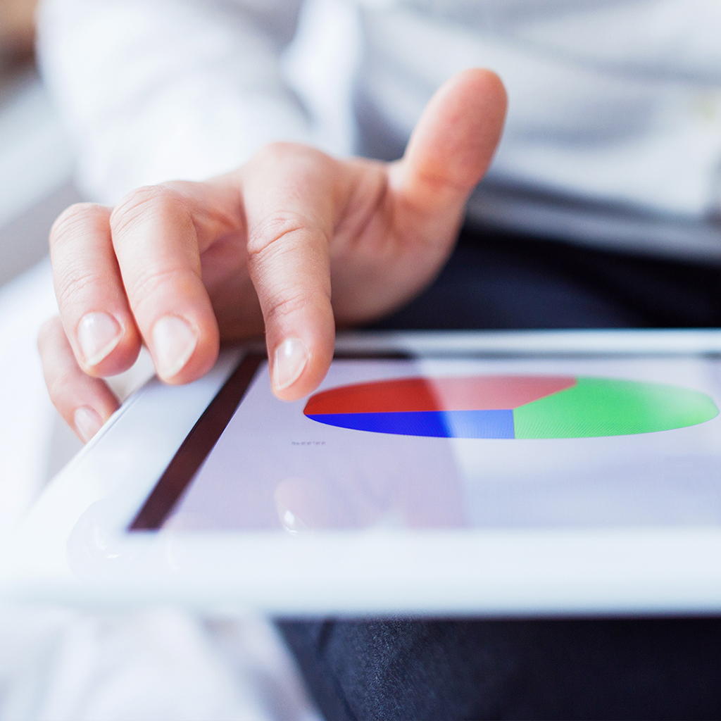 Person's hand hovering over tablet display of pie chart.