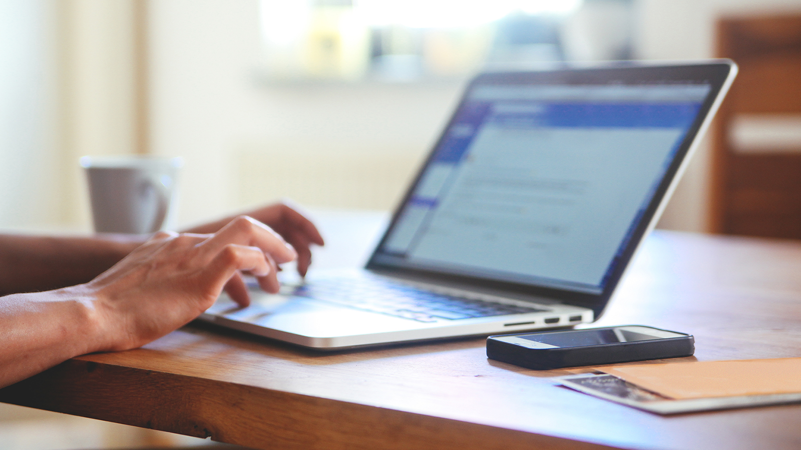 Person at table using a laptop with a smart phone, papers and coffee cup nearby.