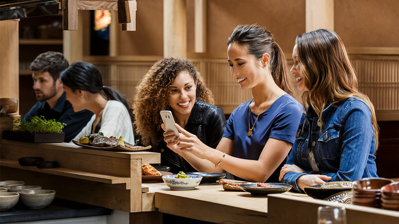 Three friends sitting in a restaurant looking at a smart phone together