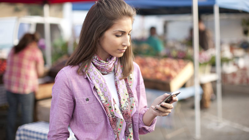 Nicely dressed woman looking at her phone while standing in a market